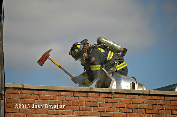 fireman on roof with an axe
