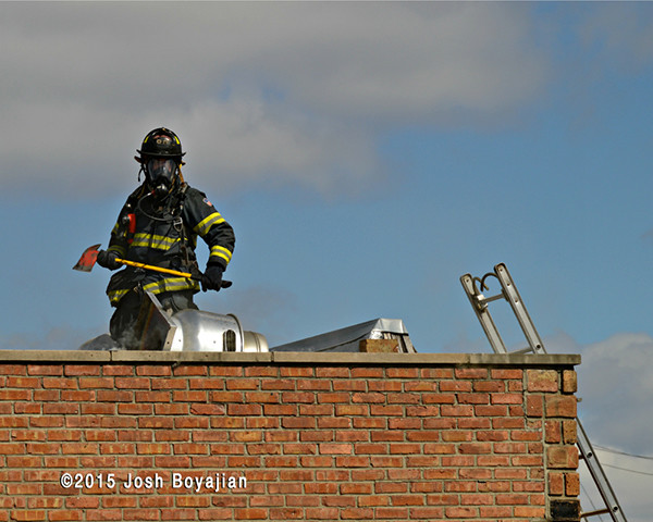 fireman on flat roof with axe