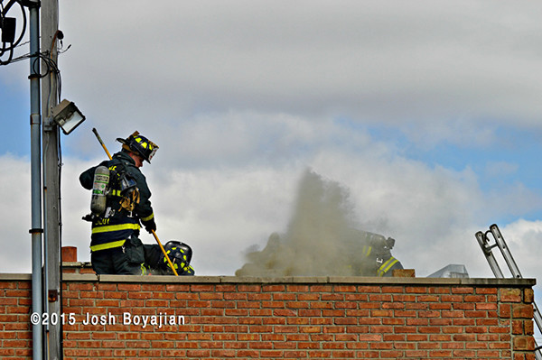firemen on roof with smoke