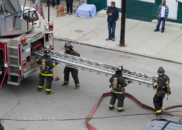 firemen remove ladder from truck