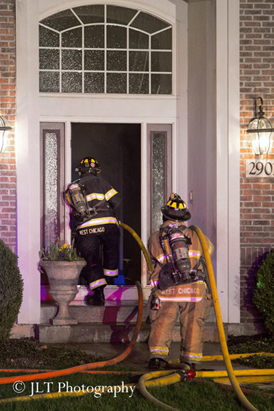 firemen with hose line at night fire scene