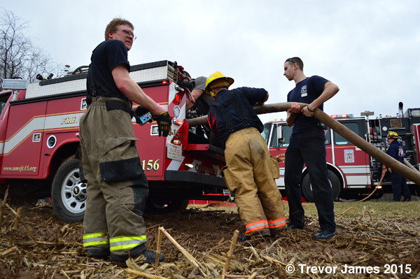 firemen add water to a fire departmetn brush truck
