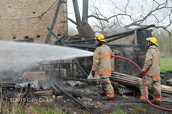 fireman with hose after fire destroyed a barn