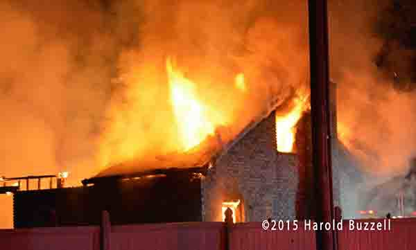 rural house engulfed in flames at night