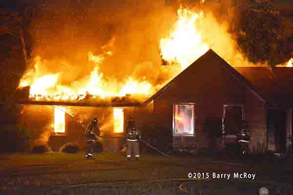 firemen battle a rural house engulfed in fire