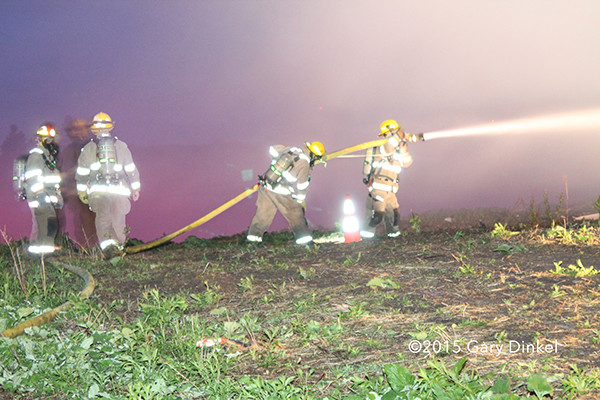 firemen with hose line at night