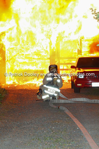 fireman about to hit garage fire at night
