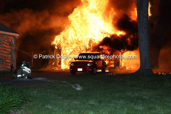 fully engulfed garage burns at night
