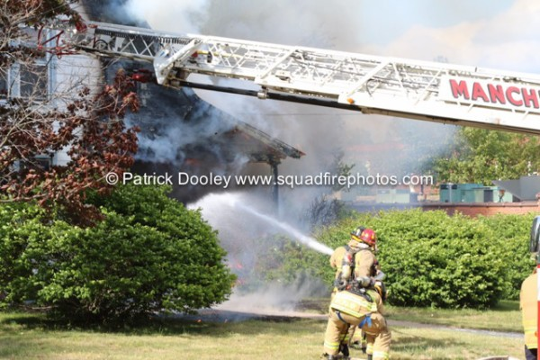 fireman with hose battles house fire