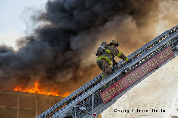 Detroit fireman climbing aerial ladder with smoke and flames
