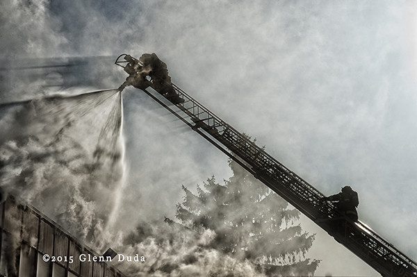 fireman works from the tip of an aerial ladder