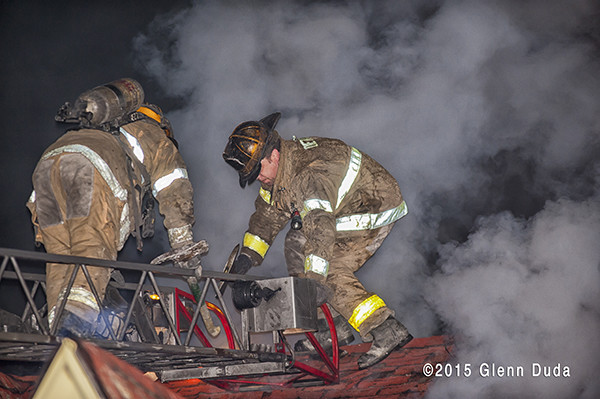 firemen on roof with heavy smoke at night