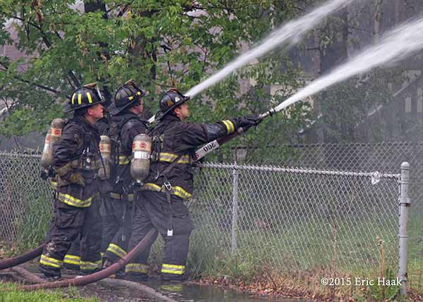 firemen with hose lines a t fire scene