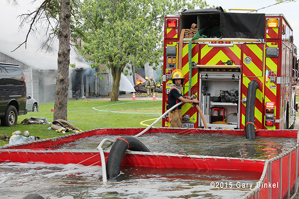 firemen dump water from a tender into a portable tank at a fire scene