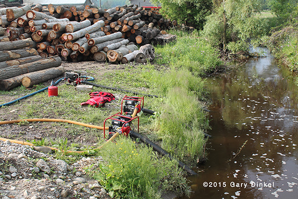 firemen use portable pumps to draft from pond