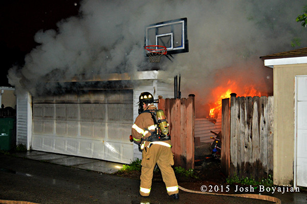 firemen attack fire in an alley garage at night