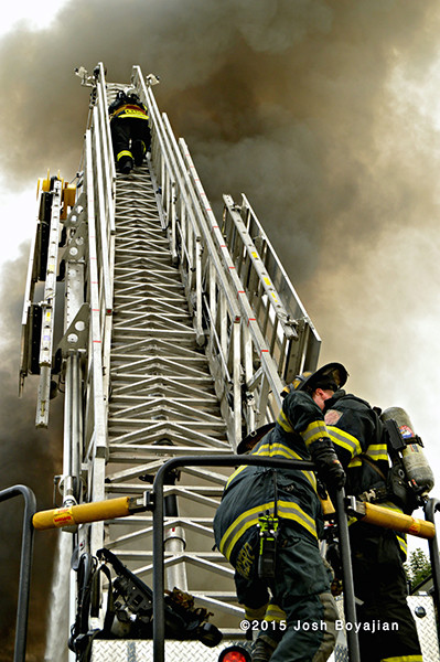 fireman climbs E-ONE aerial ladder at fire scene