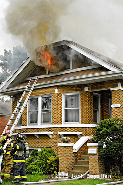 flames through attic of house on fire