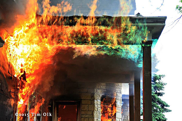 flames roll along porch of burning house