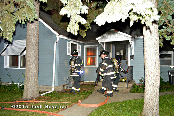 firemen prepare to take a line into a burning house