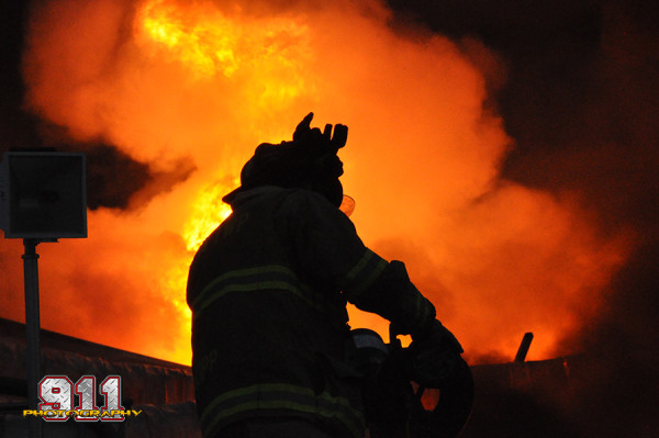 silhouette of firemen at fire scene
