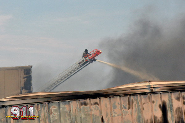 fireman on aerial ladder tip at fire scene