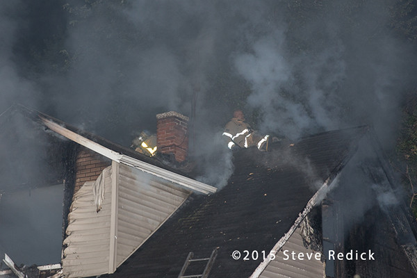 fireman on roof of house fire at night