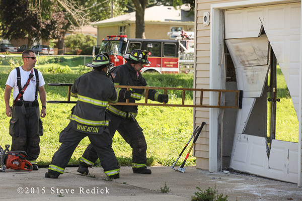 firemen use ladder to force garage door