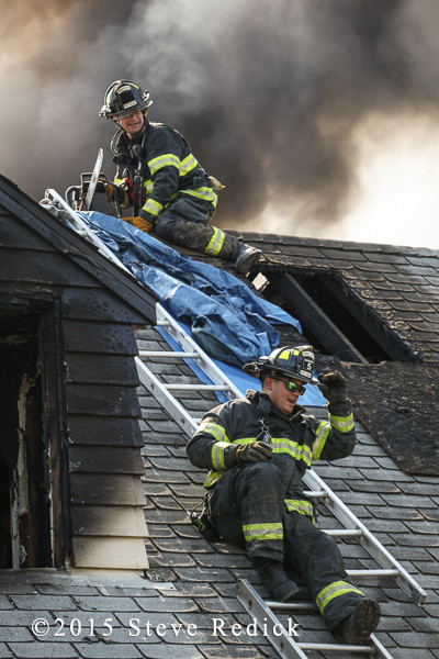 firemen on roof of house with salvage tarp