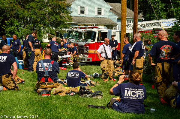 firefighters hydrate on a hot day after fighting a fire