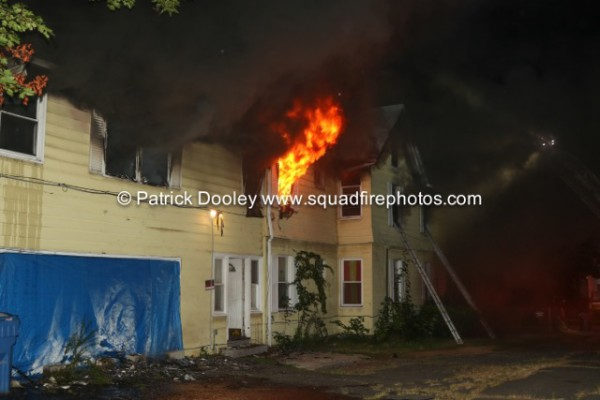 flames from windows of house at night