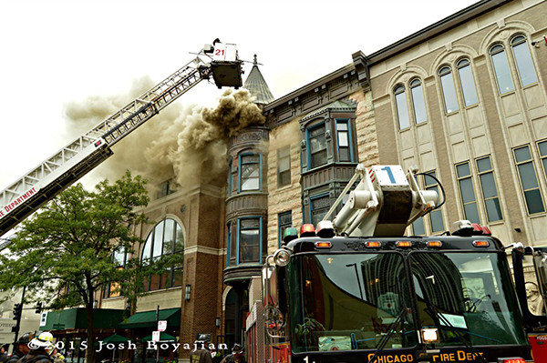 firefighters use tower ladder and a Snorkel to battle a fire
