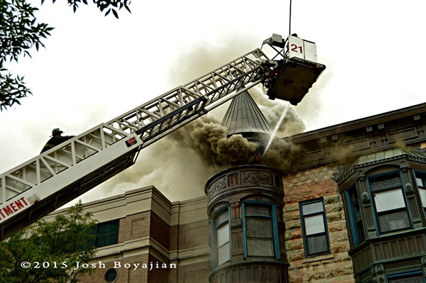 firefighters use tower ladder to battle a fire