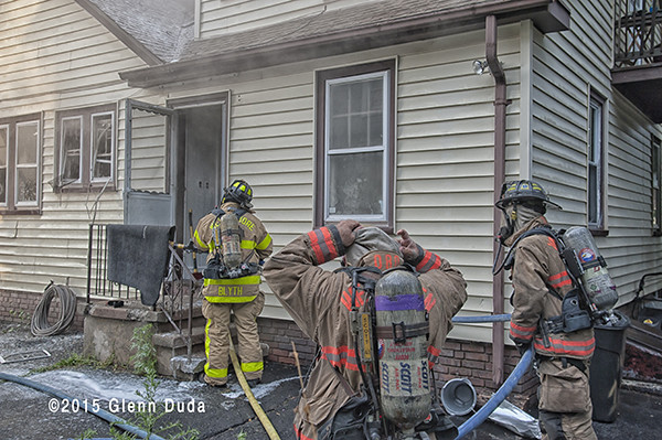 firemen donning SCBA to enter house fire