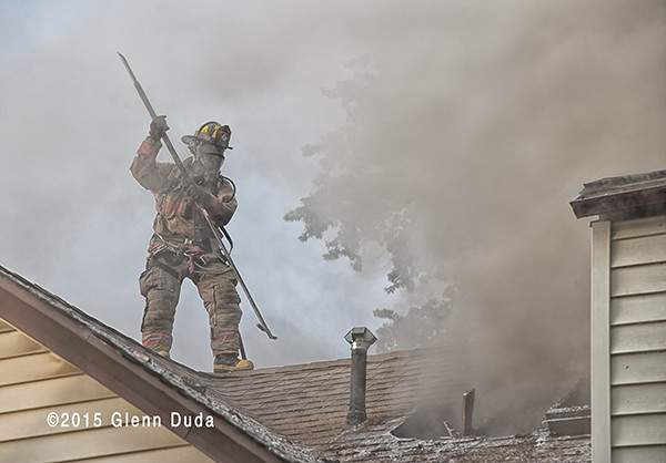 fireman in smoke on roof of house fire