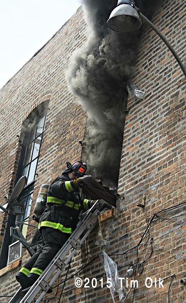 fireman on ladder at window with smoke