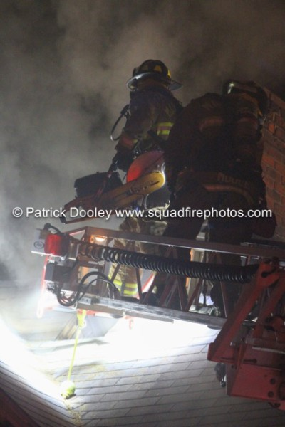 firemen on ladder tip at night
