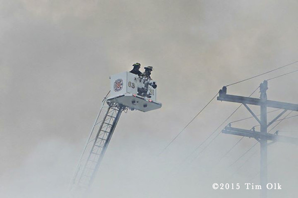 firemen in tower ladder platform with heavy smoke