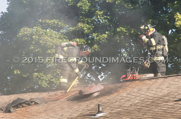firemen vent roof during house fire
