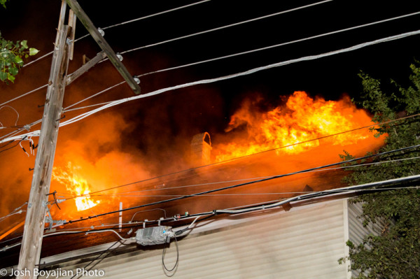 heavy fire burns through house roof