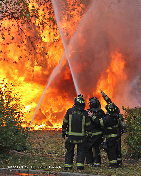 firefighters with hose at massive fire
