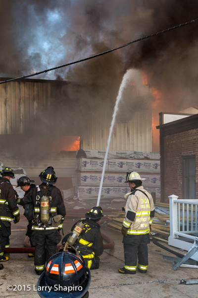 firemen with master stream at lumber yard fire