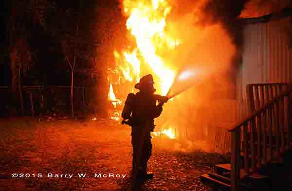 firefighter with hose silhouetted by flames
