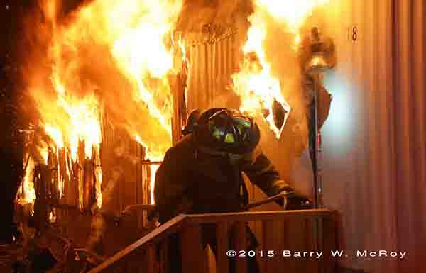firefighter breaching door of a single wide mobile home on fire