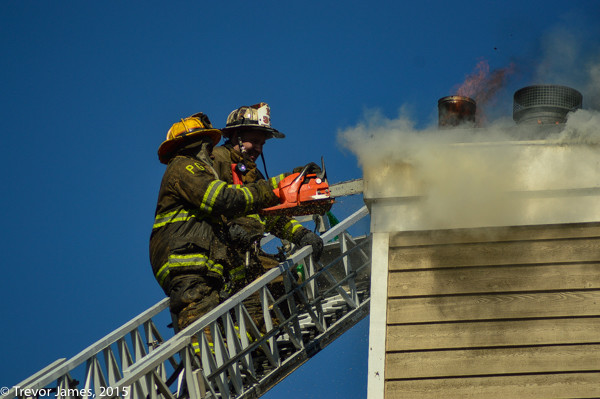 firemen on ladder with saw