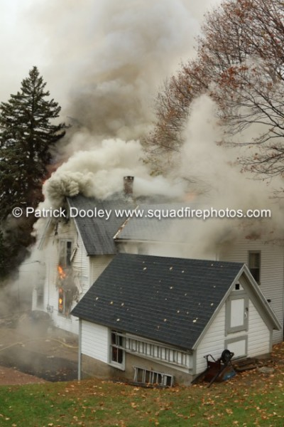 thick smoke blowing out of attic of a house