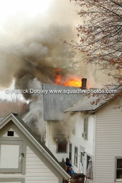 fire blowing out of attic of a house