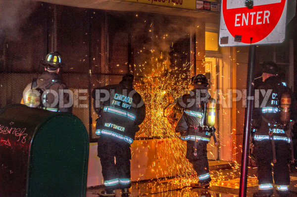 firemen cutting a metal gate at night