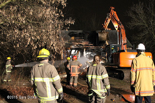 excavator tears down vacant house after fire
