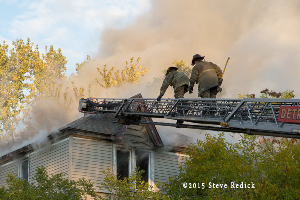 firemen climb aerial to vent house roof during fire